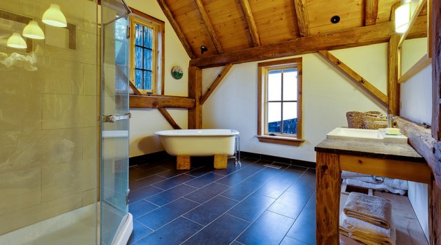 Bathroom with refinished claw foot tub and barn board trim in a  home converted