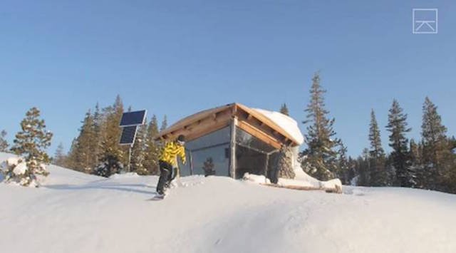 Mike Basich snowboarding outside his tiny but awesome off-grid cabin