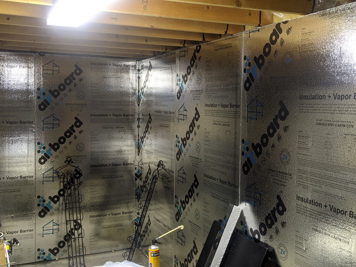 Insulating basement walls with foam bare concrete foil faced
